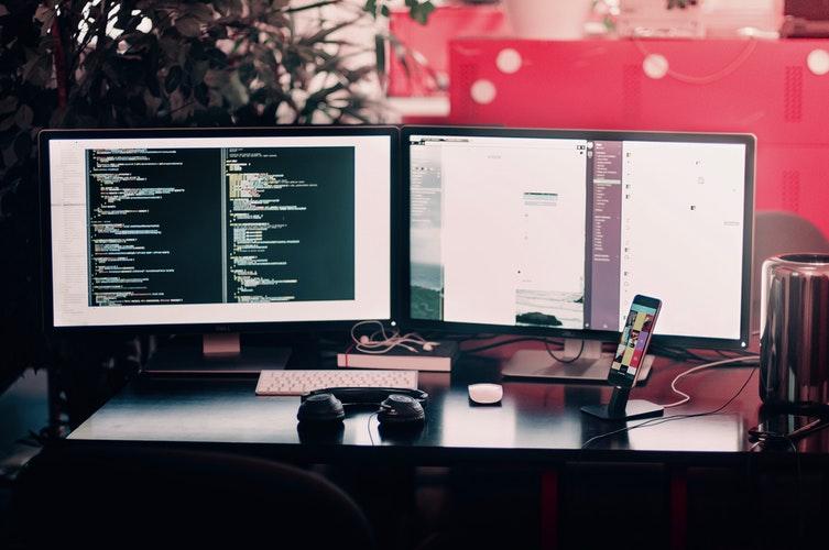 Foto de dois monitores com programas abertos