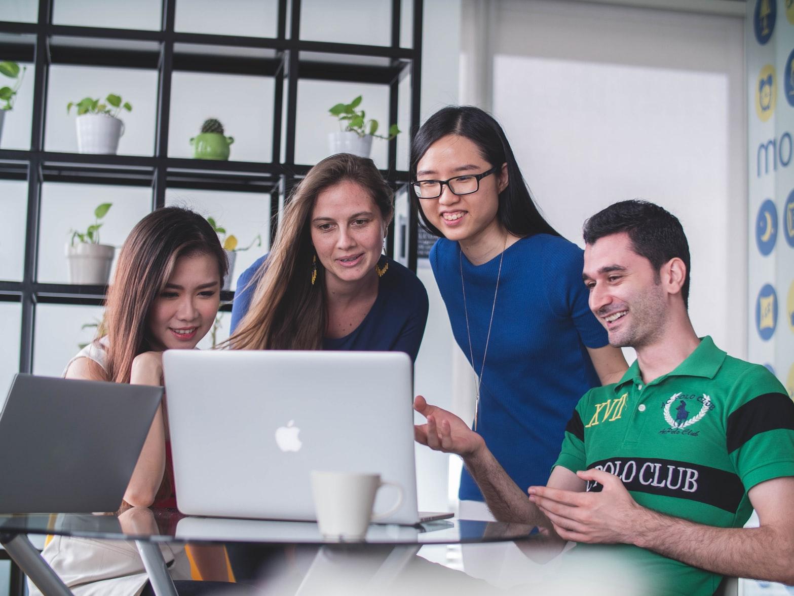 Quatro pessoas dialogando e gesticulando diante de uma tela de computador