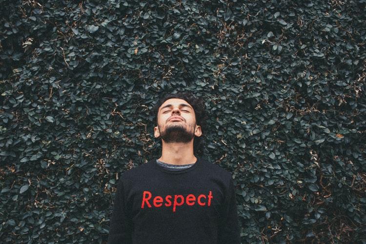 """Rapaz om camisa escrita """"respect"""" com fundo de muro de folhas olhando para cima"""