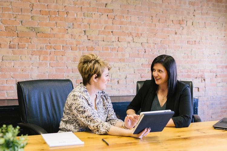 Duas mulheres sentadas diante de uma mesa conversando. Uma segura um caderno, enquanto a outra apoia as mãos cruzadas na mesa.