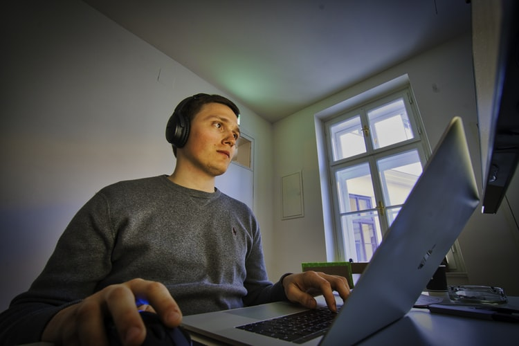 Rapaz com fones de ouvido mexendo no notebook.