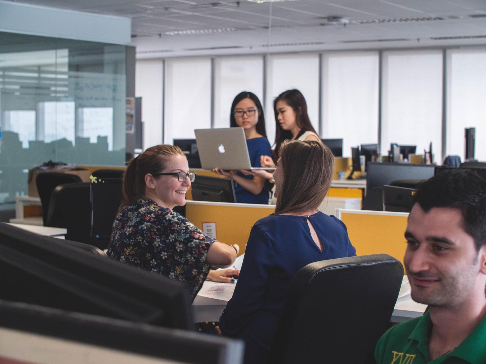 Equipe de trabalho conversando em diferentes mesas separadas por divisórias. Duas mulheres ao fundo olham para um notebook, enquanto uma delas o segura. No primeiro plano, um rapaz olha para a tela de um computador.