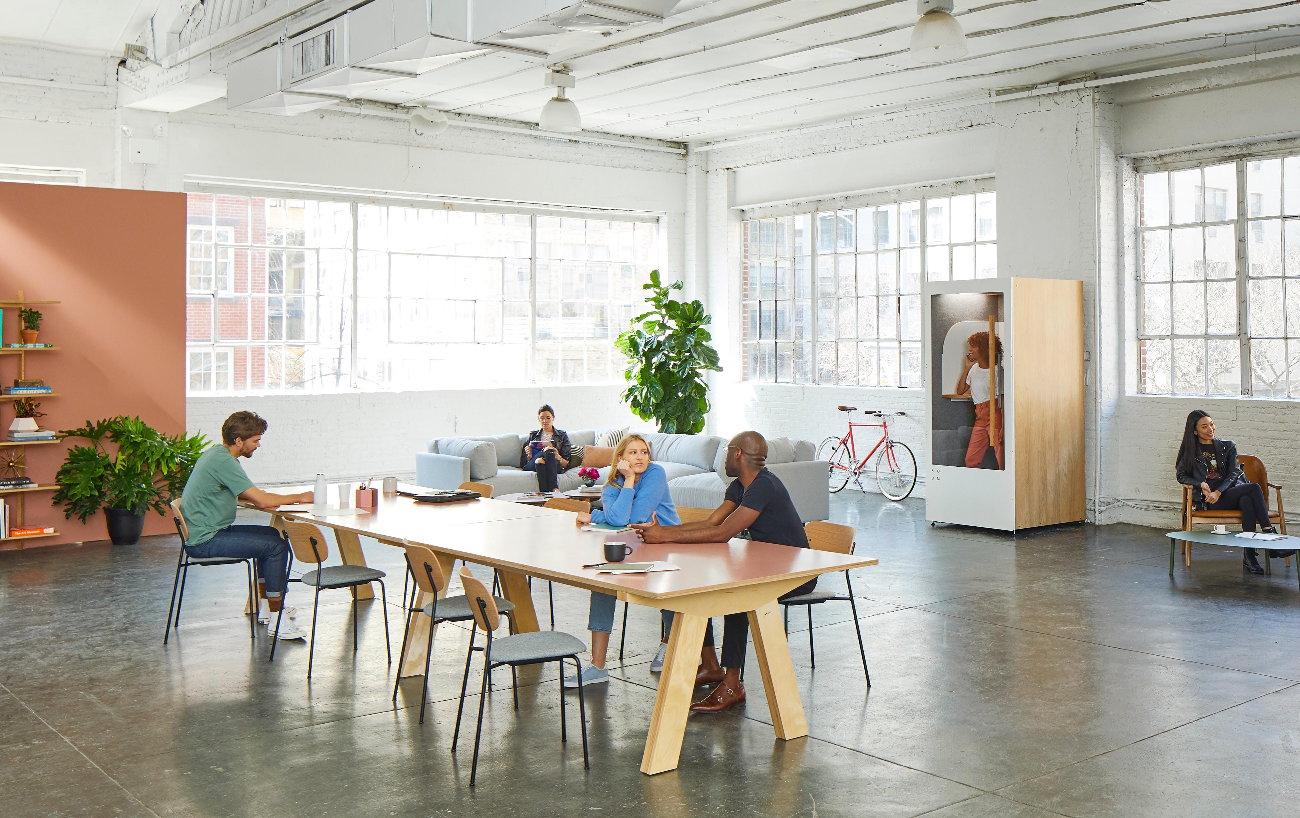 Uma sala ampla e clara com mesas, cadeiras e um sofá. Algumas pessoas estão sentadas à mesa, um rapaz sentado no sofá e uma mulher sentada em uma cadeira.