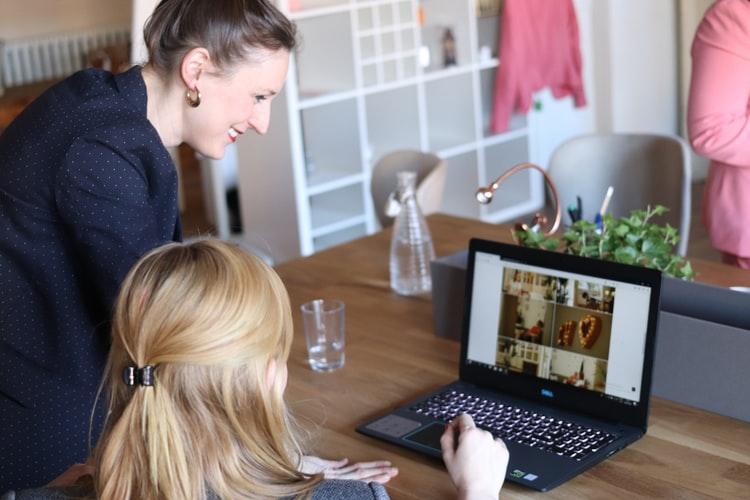 Duas mulheres olham para a tela de um notebook. Uma está sentada, enquanto a outra está de pé ao seu lado
