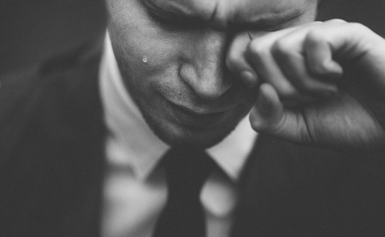 Rapaz de terno chorando