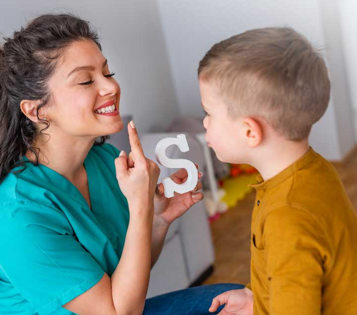 Woman showing child the letter S and teaching how to sound it out