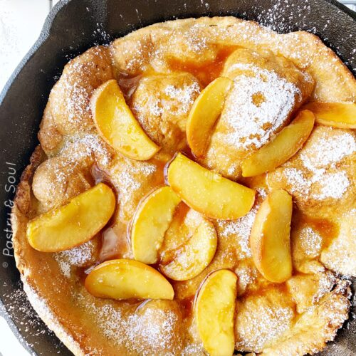 Dutch Baby Pancake in a cast iron skillet with apples in caramel sauce