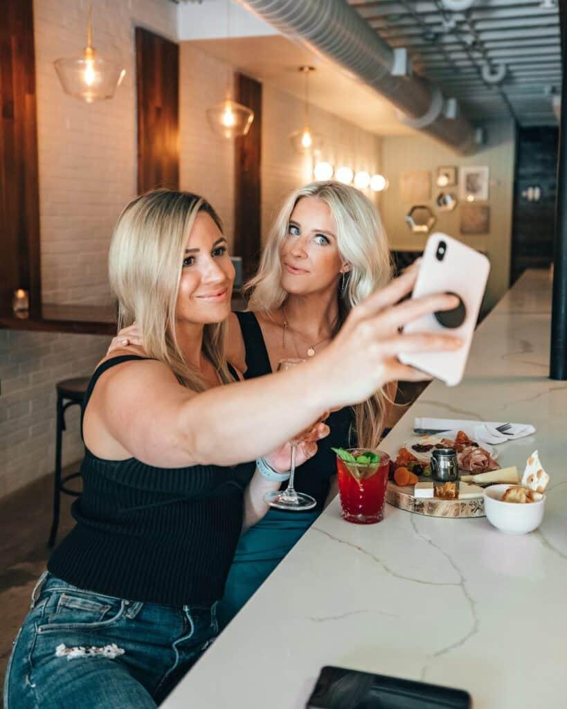 two girls taking a selfie for social