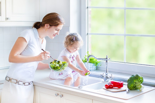 Mom and daughter washing vegetables