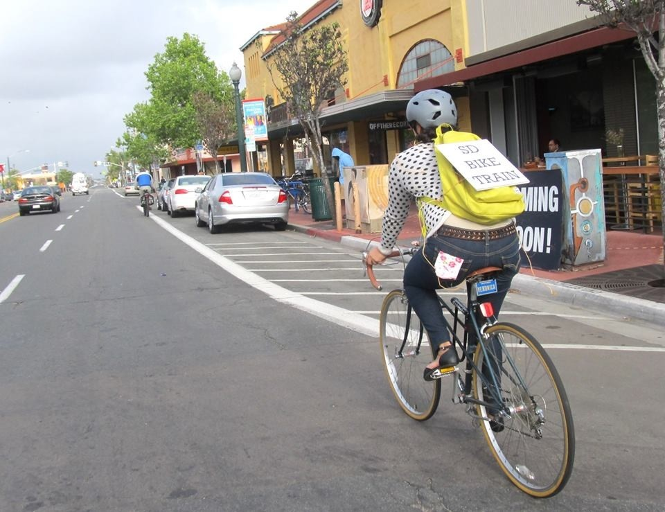 """A cyclist donning the """"SD Bike Train"""" sign rides along University Avenue. (Photo by Veronica Medina)"""