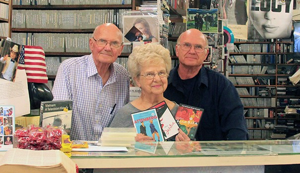 (l to r) Co-owners Rich, Winnie and Guy Hanford behind the counter at Kensington Video, which will close at the end of February after 32 years. Not pictured is Pam, Guy's sister, the store's fourth co-owner. (Photo by Hutton Marshall)