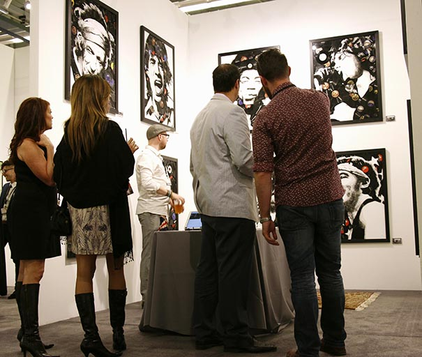 Patrons gaze at artwork featuring celebrities at the 2014 Art San Diego exhibition. (Courtesy of Art San Diego)