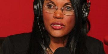 A Black woman wearing a headset and glasses in front of a microphone.