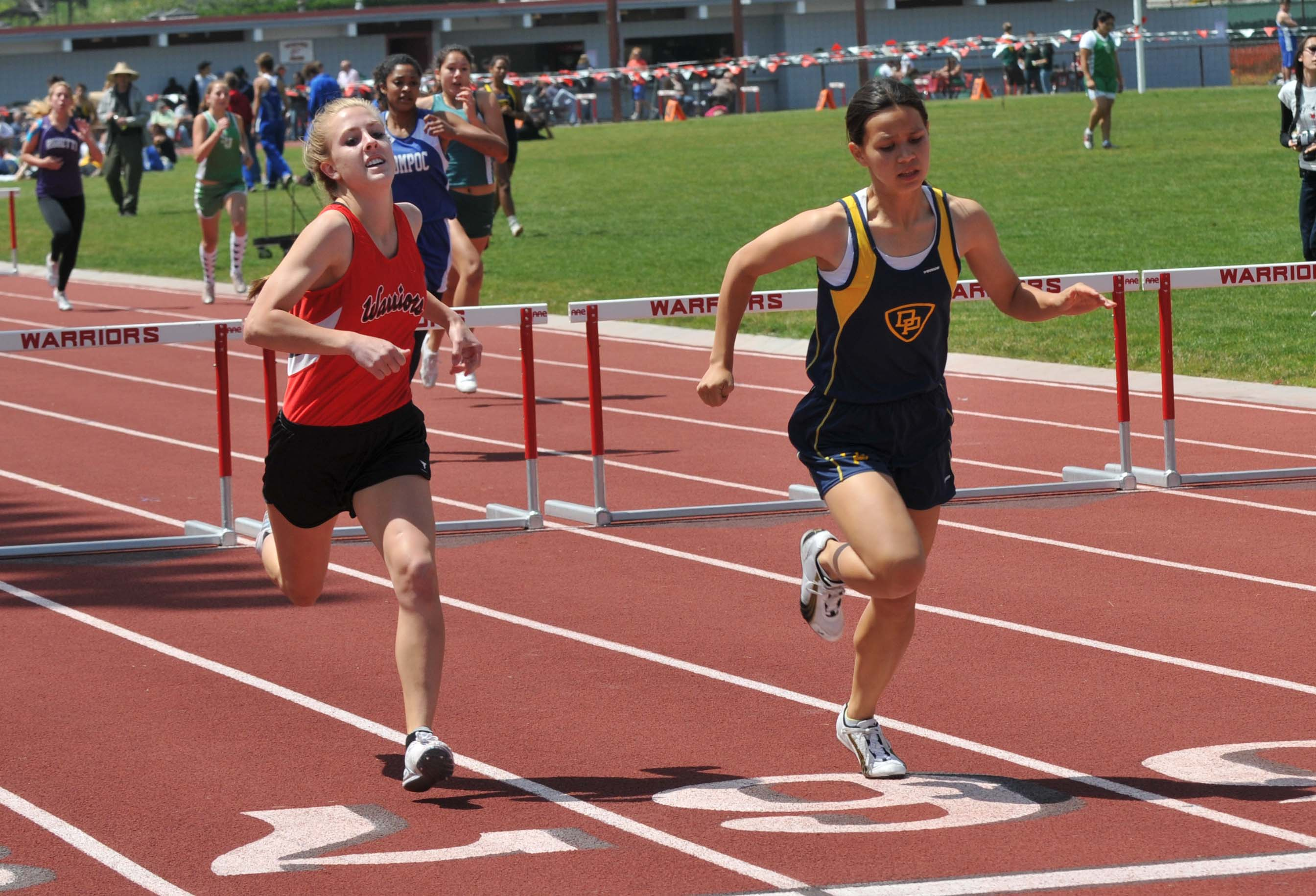 Dos Pueblos' Michelle Gee, right, edges Carpinteria's Shelby Dunlap for second place in the girls 300 hurdles.