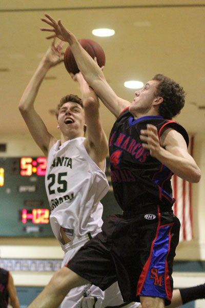 Dons forward Jack Baker fights through the tough defense of Paxton Ridgeway for a bucket in the first quarter.