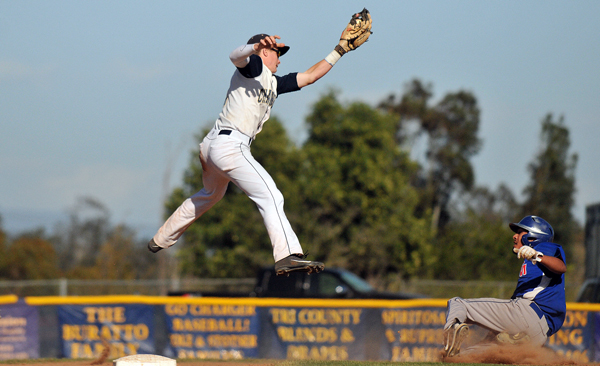 Dos Pueblos shortstop Ben York leaps to catch a throw from catch Luke Coffey. San Marcos baserunner Isaac Rodriguez was safe under the tag. (Presidio Sports Photo)