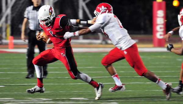 Bishop Diego's Anthony Carter tries to get around the tackles on Friday.
