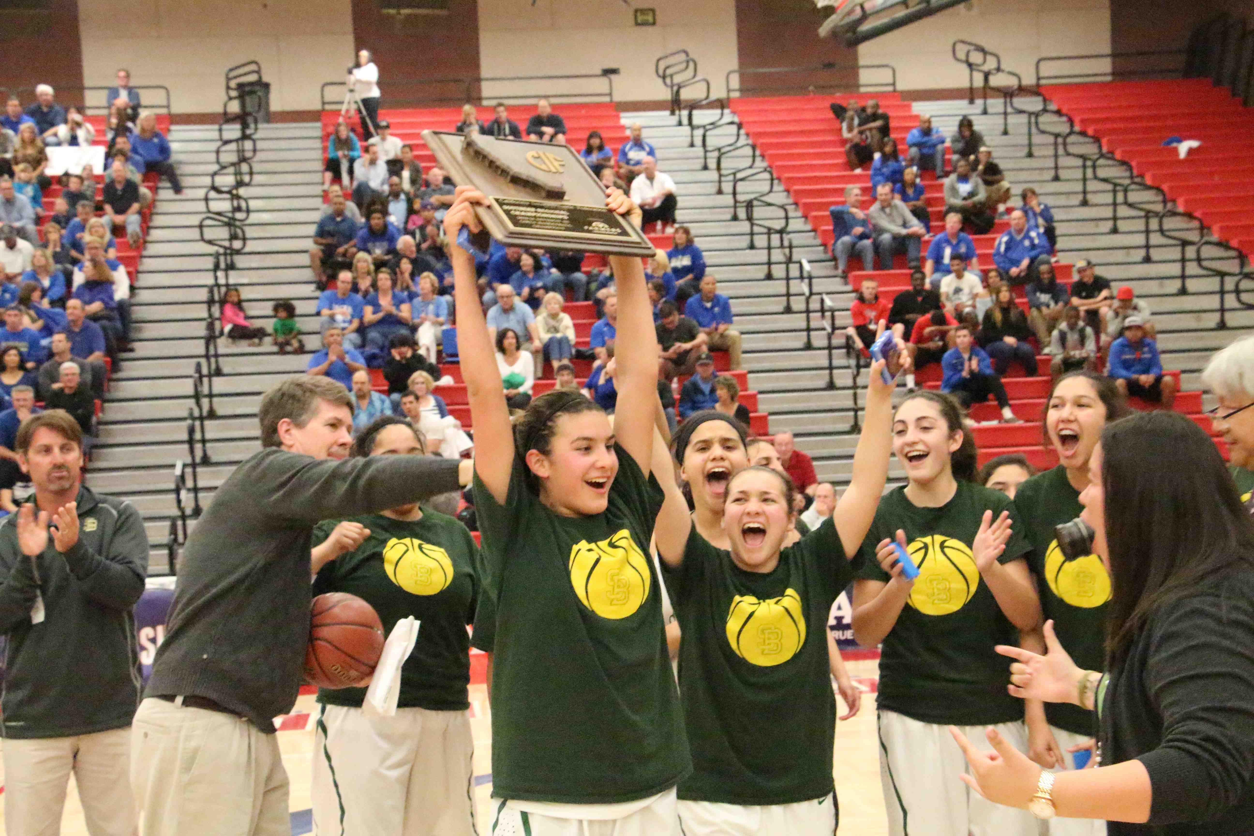 Amber Melgoza holds up the CIF Regional title plaque as her  Santa Barbara teammates celebrate after beating Santa Margarita, 58-48, in the Division 3 regional final.