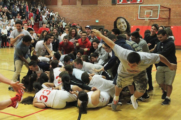 Members of the Bishop Diego football team storm the court and bowl over girls basketball team after its state tournament victory over Bakersfield Christian on Wednesday night (Photos by Thomas Salgado Jr.)