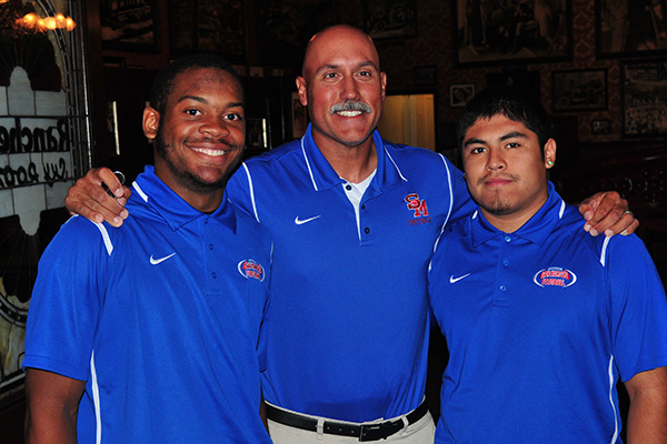San Marcos football coach Anthony Linebaugh is joined quarterback D'Shaun Vines, left, and running back Ivan Reyes.