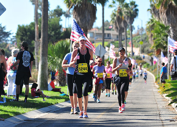 Runners approach the finish area of the Santa Barbara Half Marathon. The final mile is lined with American flags in honor of Veterans Day. (Presidio Sports File Photo)