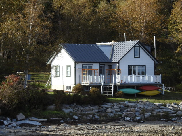 A small white house along a rock coast is shown with INroof.solar panels 80% installed.