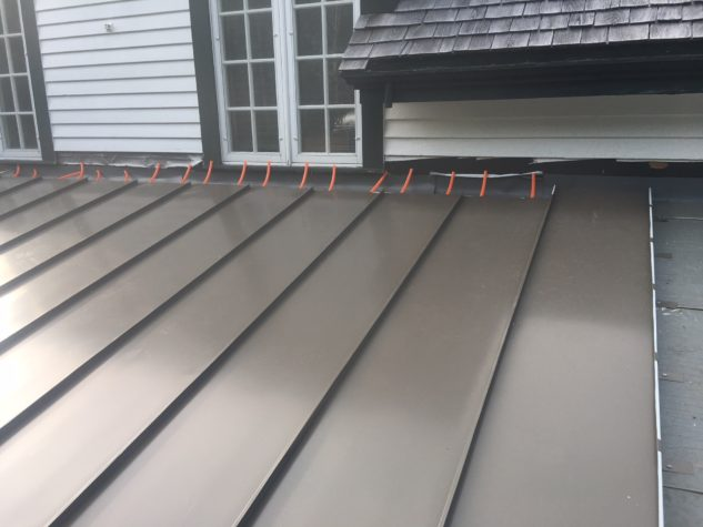 Installed INroof.solar standing seam metal roofing panels with solar thermal plumbing connections still visible before their connection