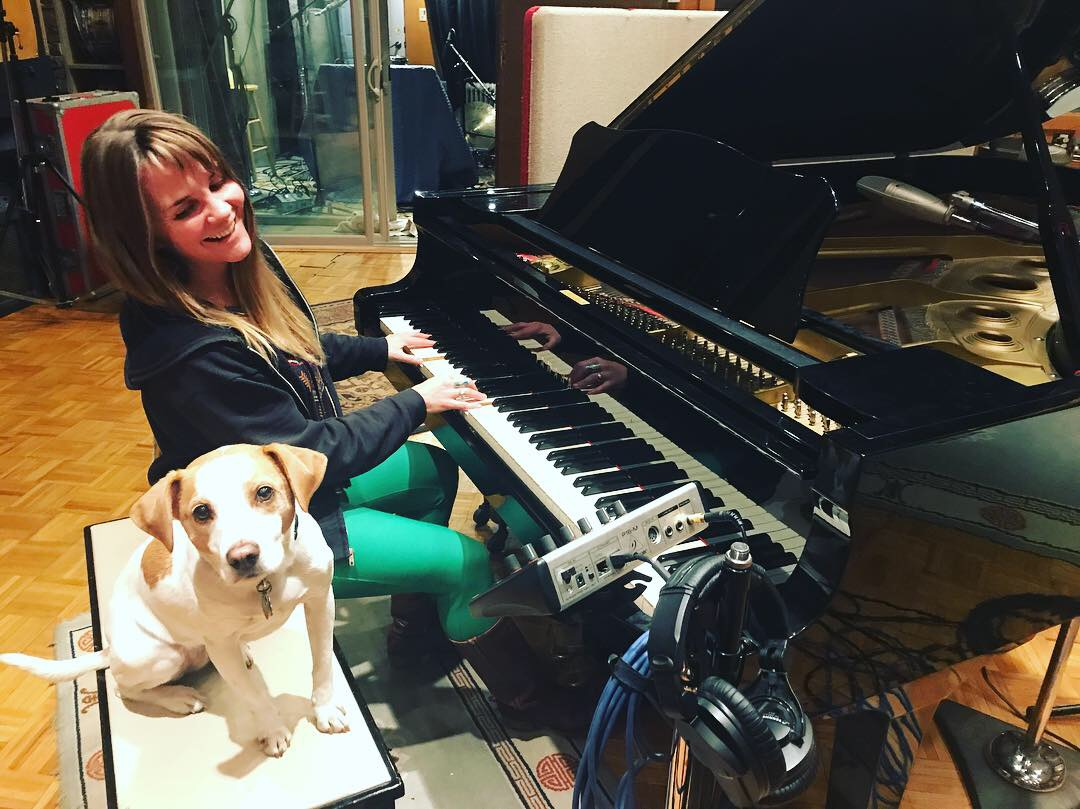 Mary Bue at piano with puppy