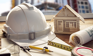 safety helmet blue print plan and construction equipment on architect and engineer working table with building construction and crane background use for construction industry business and cilvil engineering