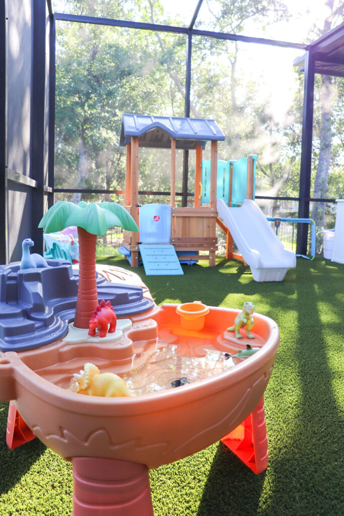 step2 playhouse, artificial turf play area, screened in play area, outside play area for kids, backyard play area for kids, shaded play area for toddlers, toddlers outside play area, mud kitchen