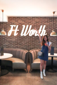 alexandria holding a drink standing in front of a fort worth sign