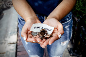 """a woman's cupped hands full of various coins and a piece of paper that says, """"mage a change""""."""