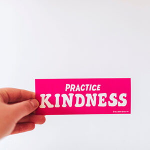 """a hand holding a pink sign that says """"Practice Kindness"""""""