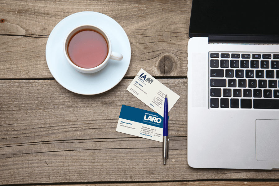 Business cards on table between laptop and cup of tea