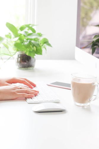 plant in office with woman at computer and coffee
