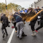 Anti Fascists and True Blue Crew members are pepper sprayed to break up a fight during a 'Say No To Racism' protest and a counter 'Stop the Far Left' rally.  Seven men were arrested after a violent brawl erupted between rival protesters.
