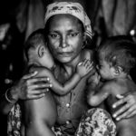 A distressed mother named Shamijder (age 30) holds onto her twins aged 1 year whom both suffer from malnutrition. An estimated 110,000 ethnic Rohingya live in an overcrowded IDP camp in the outskirts of Sittwe.  The Rohingya continually make attempts to flee the camps by fishing boat and seek asylum in neighbouring Islamic countries however often fall victim to human traffickers. At current they are a stateless people believed to be illegal immigrants from Bangladesh. According to the UN the Rohingya are one of the most persecuted minorities in the world.
