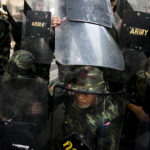 25/05/2014. Thai army duck for cover using their shields after anti-coup protestors threw bottles of water following a Anti-Coup protest in Bangkok Thailand.