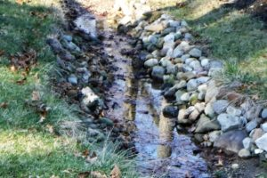 small creek lined with large rocks protecting the creek banks
