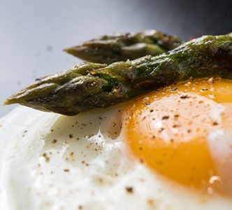 Fried egg and roasted fresh  asparagus in black plate