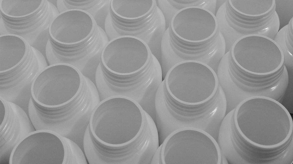 vitamin bottles on bottling line for custom label private label manufacturing of nutritional supplements
