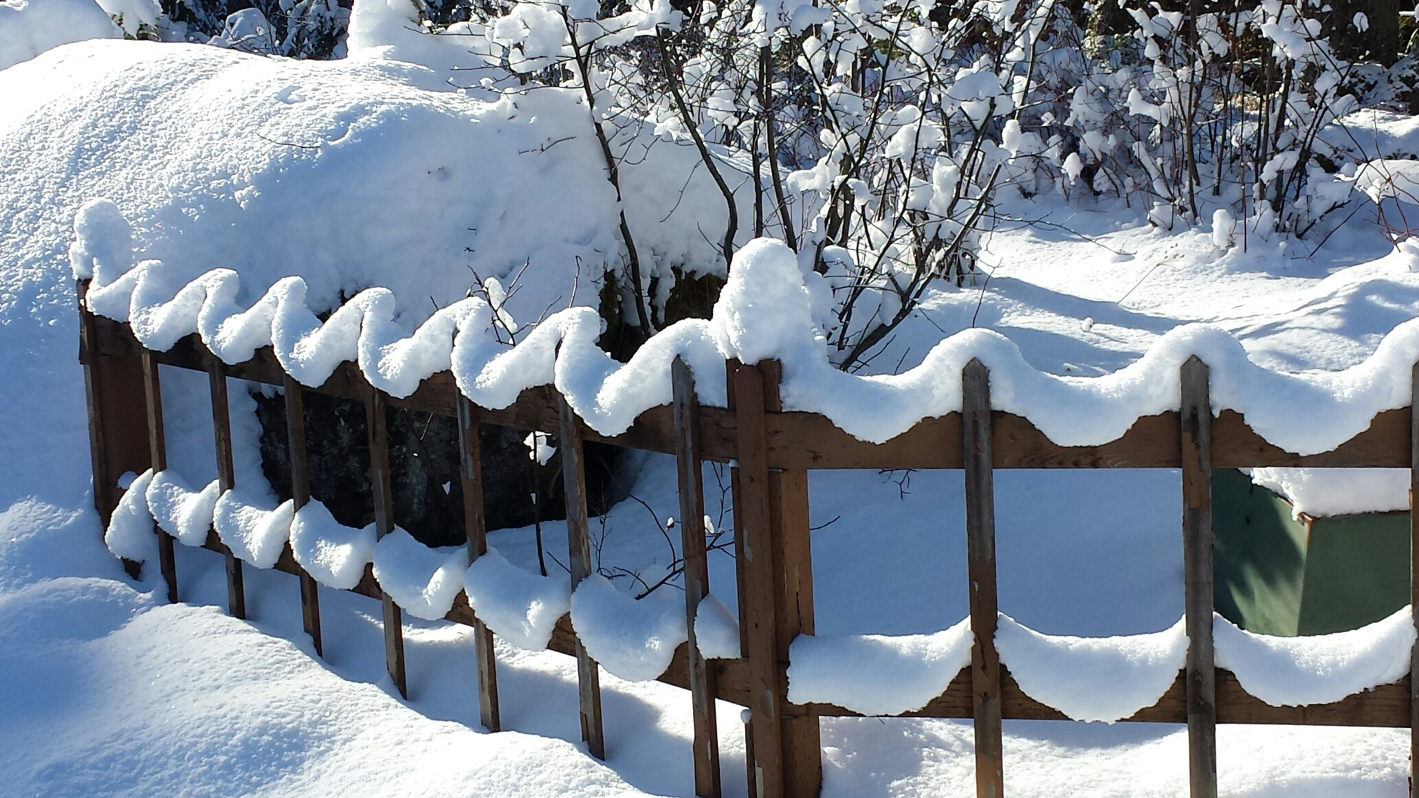 Photo of snow decorating a picket fence in Juneau, Alaska.