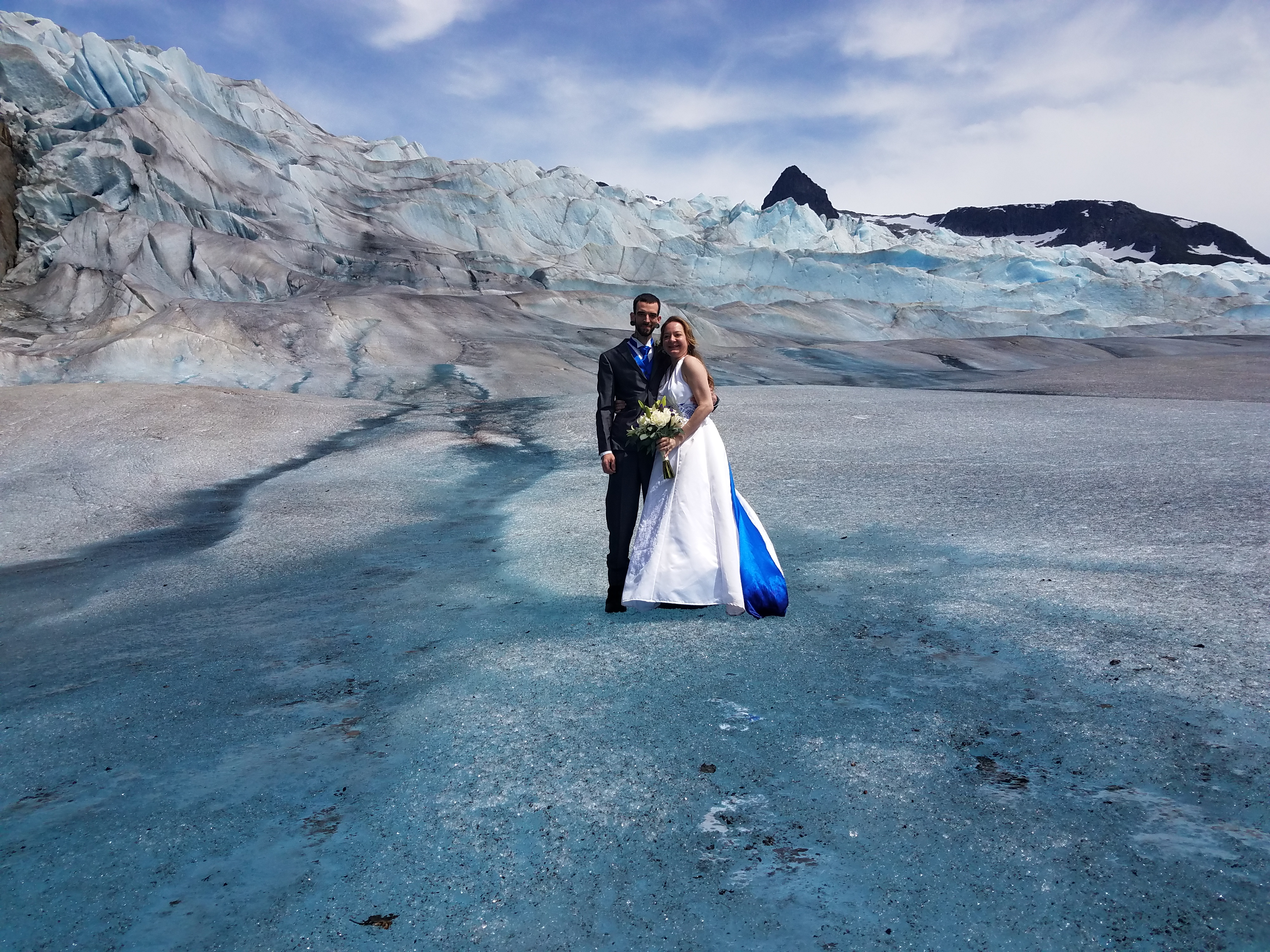 Photo of a glacier wedding couple on the blue ice of Mendenhall Glacier in Juneau, Alaska.