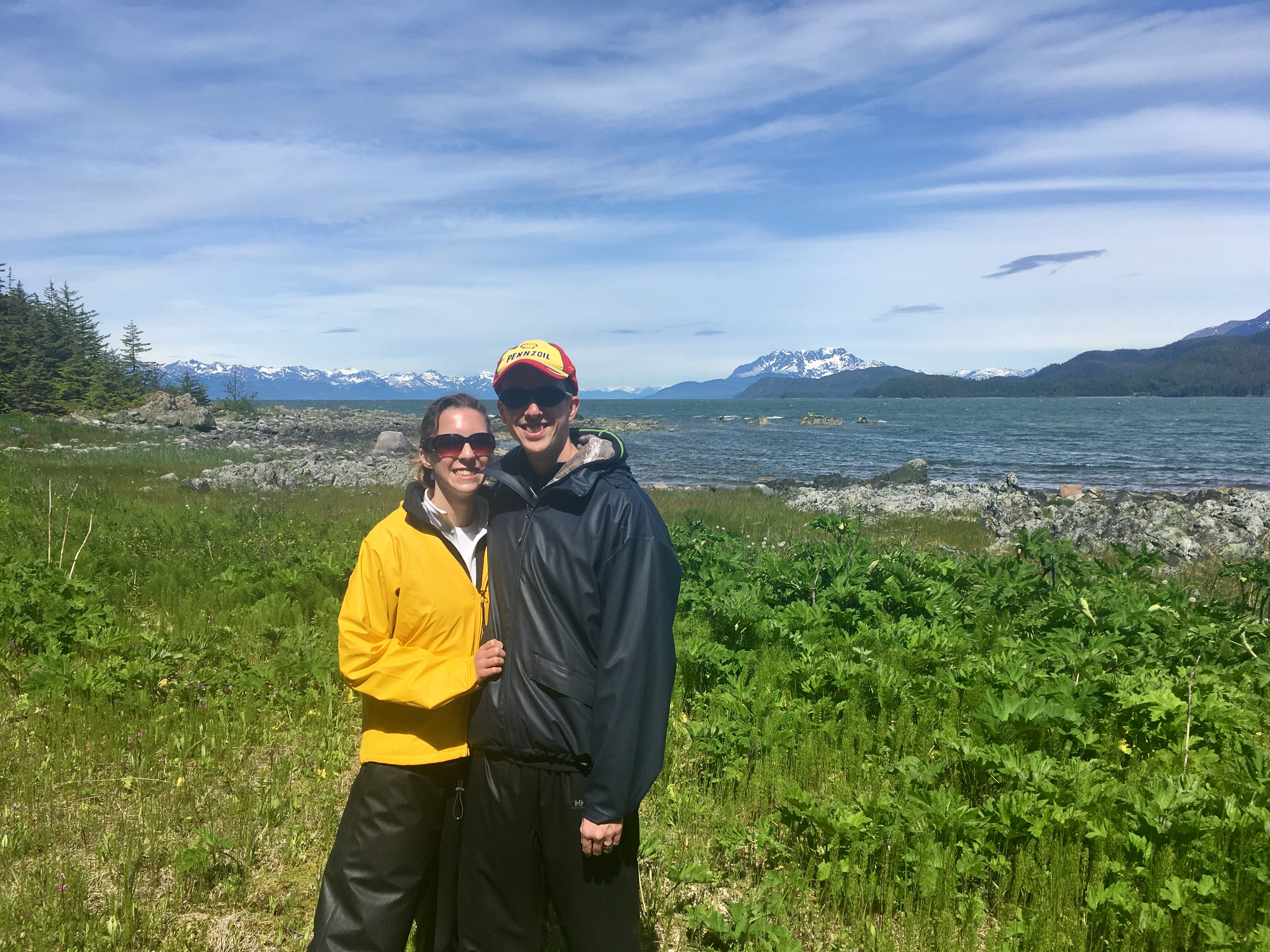 Photo of a couple standing on an island with the channel and snow-capped mountains in the background
