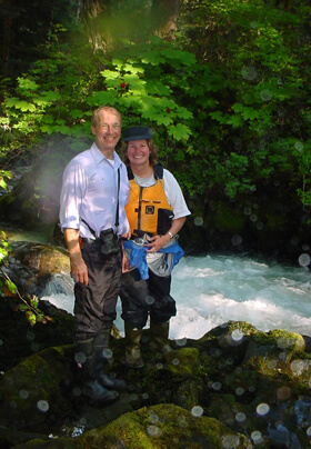 Photo of couple hiking along a salmon stream in Juneau, Alaska.