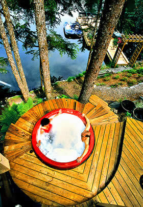 Couple relaxing pondside in one of the outdoor rain forest hot tubs.