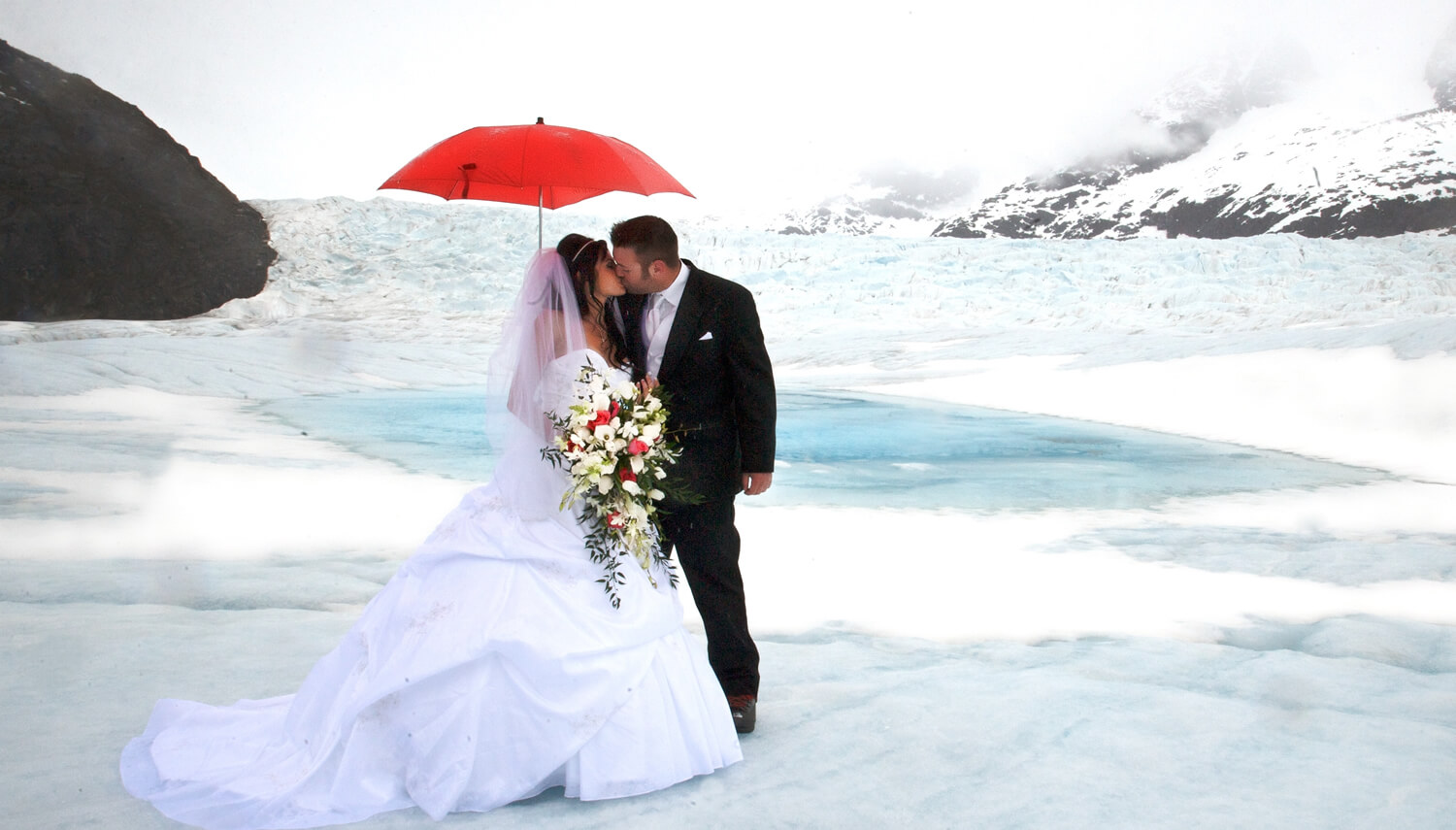 First kiss on the glacier beside a clear blue glacier pond under a bright red umbrella