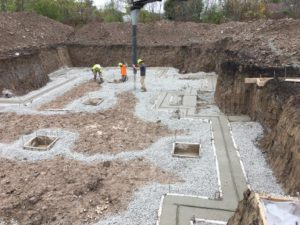 Using conveyor to stone footings for new home foundation