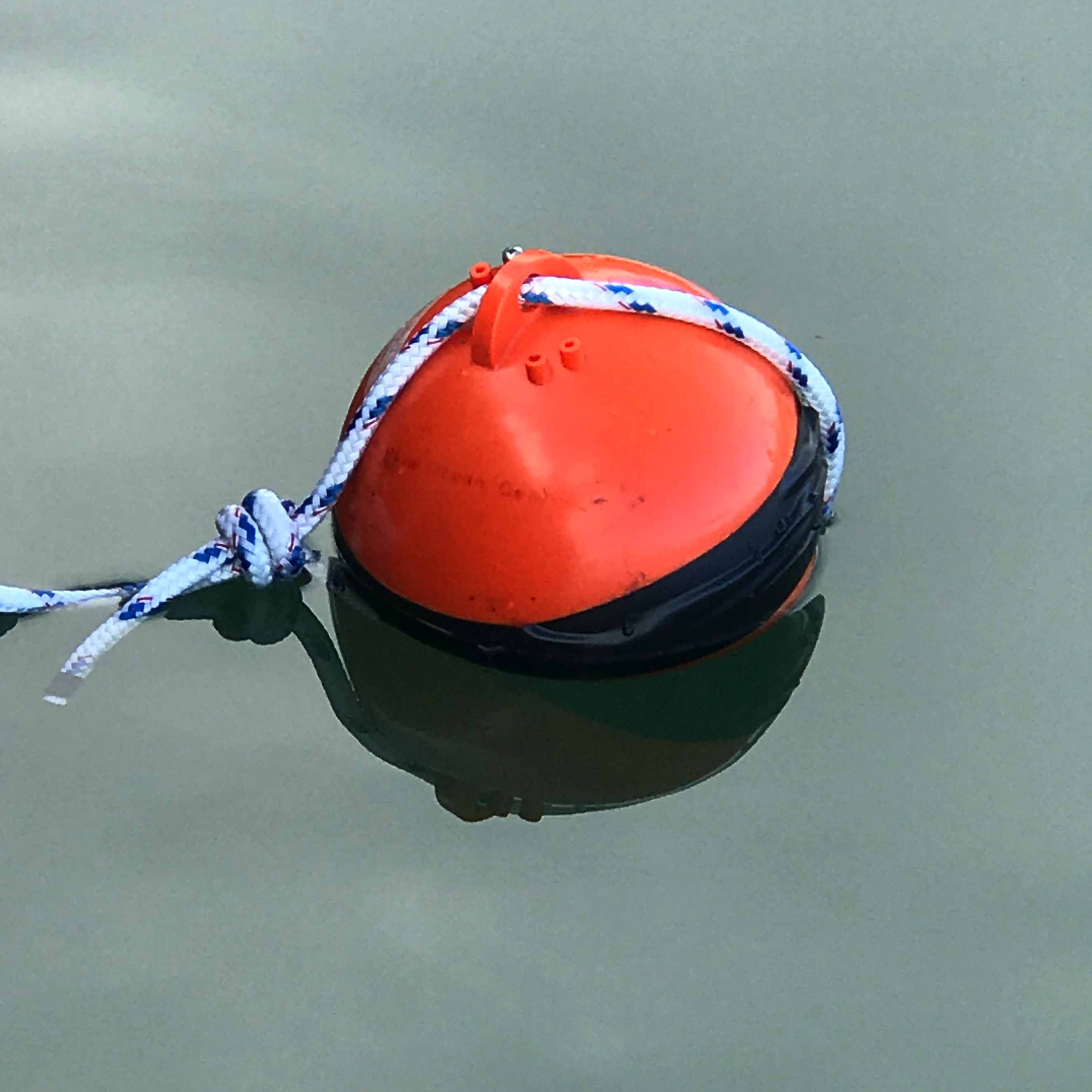 Orange Blue Ocean Gear Smart Buoy on calm water