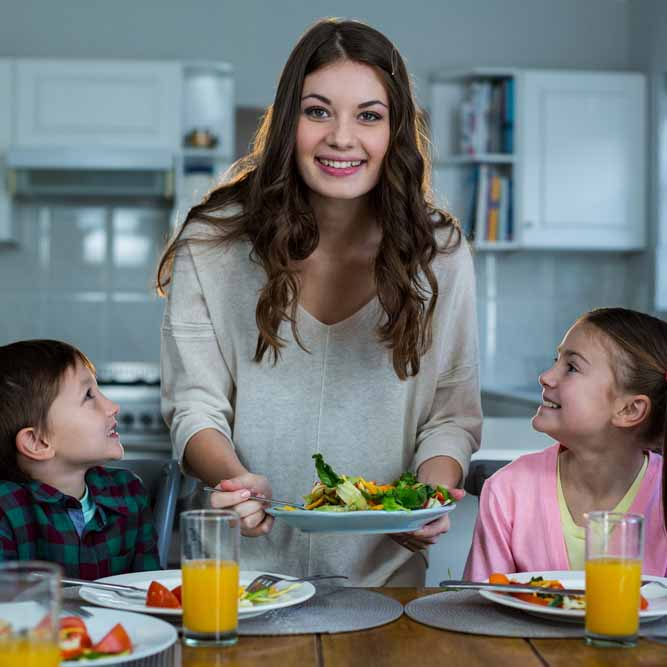 Mother serving breakfast to their children in kitchen